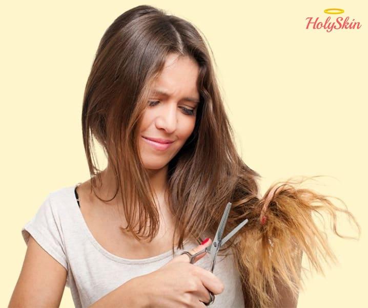 Девушка отрезает сечёные кончики волос