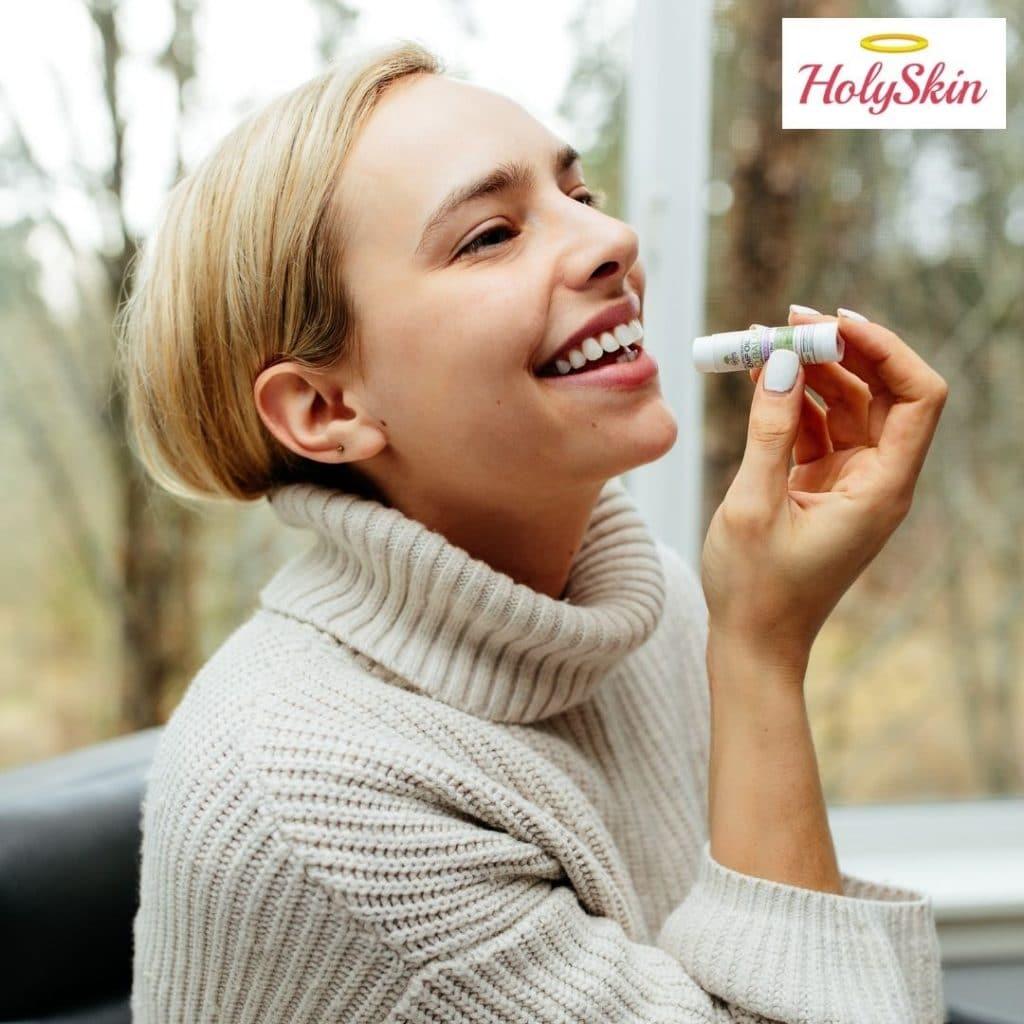 Девушка пользуется восстанавливающим бальзамом для губ