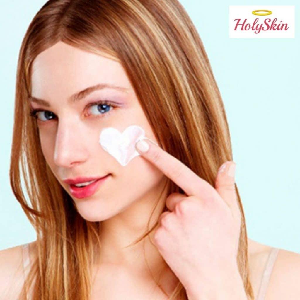 Девушка наносит крем для кожи вокруг глаз